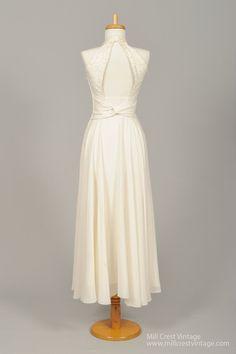 Conçu dans les années 60, cette robe de mariée vintage fantastique est faite dans une dentelle florale avec bande de crochet dans le corsage et une jupe de mousseline poly sur une doublure en soie poly mélange de glissement. Le corsage sans manches offre un décolleté licou de style avec ligne de buste col en v plongeant et dos de trou de serrure et est garni de boucles. Une bande de dentelle au crochet orne la taille, doù la mousseline de soie jupe tombe à propos de longueur de thé. Une…