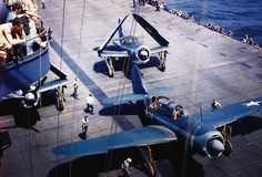 Two Navy Helldiver planes on the deck of an aircraft carrier, one with wings extended, one with wings folded.