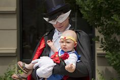 A parent dressed as Tuxedo Mask cradles a baby Sailor Moon.