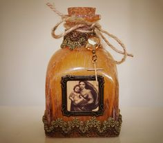 Rustic decor bottle is a gorgeous shade of amber!  It features image of Madonna and Child, framed in bronze metal.  Bottle is trimmed in ornate antique French metallic ribbon, vintage cross, pretty square amber crystal bead and a twine bow