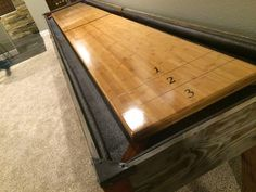 Custom shuffleboard table with burnt wood, leather and bamboo by Ginger Hawk Customs.
