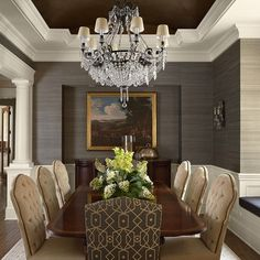 Classy dining room with recessed ceiling painted a dark color, with textured wallpaper, and glamorous chandelier