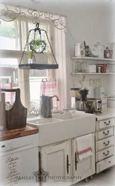 Beautiful farm sink adds beauty to this cute shabby kitchen..