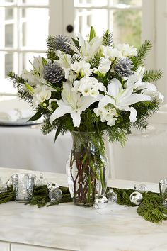 Turn your holiday buffet into a winter wonderland with full, white bouquets, pine sprigs, and garland.