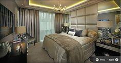 Luxury bedroom - Padded wall height headboard, recessed  lighting, mirrored feature walls