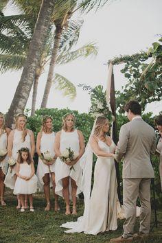 NATALIE DEAYALA BRIDESMAIDS. our silk high neck hi-lo dresses in sugar are perfect for this all white beach wedding.  Photography: Kellie Kano - http://www.stylemepretty.com/portfolio/kellie-kano Groomsmen's Attire: J.Crew - jcrew.com Groom's Attire: J.Crew - jcrew.com   Read More on SMP: http://www.stylemepretty.com/destination-weddings/2015/10/14/romantic-bohemian-bahamas-destination-wedding/