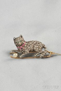 Antique Silver and Rose-cut Diamond Cat Brooch, France, with rose-cut diamond body, green beryl eyes, and ruby collar, on a pair of tongs with pearl ball of yarn, silver-topped 18kt gold mount