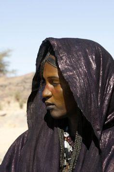 A braided hair diadem adorning the forehead of a Tuareg woman, who applied red ochre to her dark brown face.
