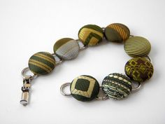 This recycled necktie bracelet is made using 8 reclaimed mens neckties in Olive, Mustard, Khaki and Cream designs.    The silvertone metal bracelet