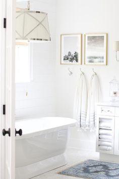 Illuminated by a Grosvenor single pendant, a beautiful white Mirolin bathtub…