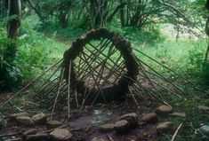 River stone supported by hazel sticks  collapsed several times  the last four or five stone being the most awkward  made across a path at the entrance to a glade  Swindale Beck Wood, Cumbria  13 September 1982