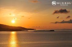 小浜島の最高峰うふだき(大岳)の展望台からの夕景。 西表島に沈み行く夕陽の右手に、水平線と重なるように鳩間島のシルエットを見ることができます。