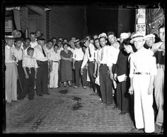 """People stand around the blood stain from John H. Dillinger, 32, in the alley behind the Biograph Theater in Chicago. Dillinger was shot and killed by FBI agents on July 22, 1934 after receiving a tip from Dillinger's friend Anna Sage. Sage, known as the """"Woman in Red,"""" told authorities that she, Dillinger, and Dillinger's girlfriend Polly Hamilton Keele would be at the movies and to look for her dressed in red. Some reports say Sage was actually dressed in orange. — Chicago Tribune…"""