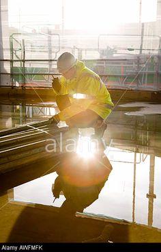 Construction site worker on a walkie talkie radio. © Craig Holmes / Alamy