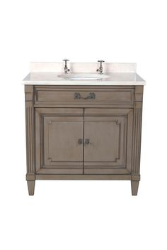 The Manoir vanity unit is shown in Cherry wood with an Antique Grey finish. The piece features two cupboard doors with one adjustable shelf and a faux top drawer with ironwork in Antique Brass.
