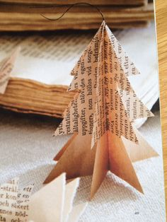 DIY Christmas tree ornament  - card cutouts of a tree, apply newspaper, music print or old book pages and voila! Rustic, simple, elegant