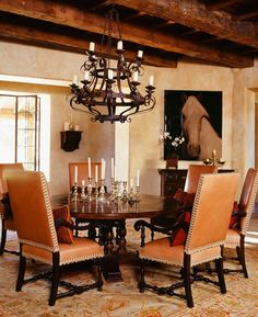 spanish colonial round table dark mahogany arm chairs iron chandelier heavy beams on