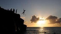 Cliff jumping in Oahu, Hawaii at sunset.
