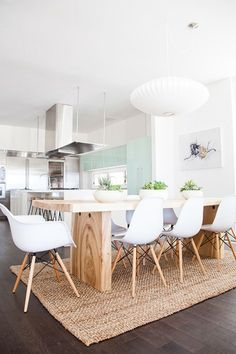 Timber table and white chairs on rug