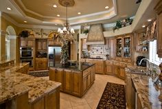 Mediterranean Kitchen with Raised panel, Limestone Tile, Columns, Complex granite counters, Glass panel, U-shaped, Stone Tile