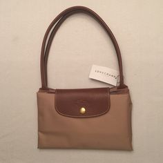 Brand new Longchamp bag Brand new with tags. Tan/brown. Folds and buttons up to be more compact. Longchamp Bags Shoulder Bags