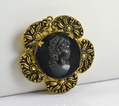 Beautiful black glass cameo locket pendant. Framed by antiqued gold tone flowers. Cameo is prong set. Cameo is appx 1 diameter. Locket will hold a picture that is 1 1/8 x 7/8. Good vintage condition with the exception that the gold tone metal shows a spot of black tarnish on back. Please see all 5 pictures as they are part of the description. There is also a zoom feature! For more fun and fabulous curiosities check here: www.chicmousevintage.etsy.com Rocks, fake fruit, candles, book...