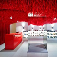 Brazilian architect Marko Brajovic has affixed thousands of bright red shoelaces to the undulating ceiling of this Camper store in Melbourne