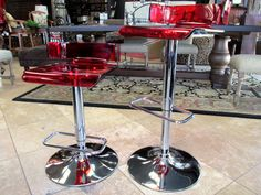"Contemporary bar stools with red Lucite seating and a chrome body. Seats swivel and bar stool adjusts for any height needed. Seat size is 16"" square. Priced at just $195.00 each(two in stock)."