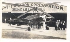 This photograph shows a plane that participated in the 1931 Grand Island Airshow at the Grand Island Airport.  This photograph was taken by James A. Tuma, the Grand Island Airport manager.  The image shows an airplane in front of a hanger.  The top of the hanger reads West Aviation Corporation Travel Air Sale Service.  Emil Wolbach is shown pictured at the far right hand side.
