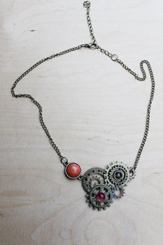 This steampunk necklace combines antique bronze gears and red stones to form a highly decorative unity. As it is unique (will not be made twice) it is suitable as a gift for yourself or for your friends and close relative. Important information: • This listing is for the necklace pictured in the first photo • Both the design and fabrication is done by me. I will not make any more copies. • The necklace is made of alloy, glass beads and acrilic stone. • Due to the glue used, please dont place…