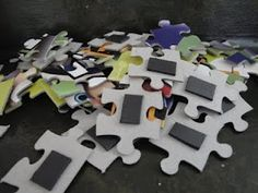 Put magnets on the backs of puzzle pieces and use on a wall magnet board.