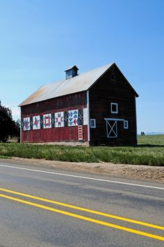 A barn with quilt block panels sits along the road in Yamhill, Oregon, USA.