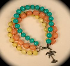 3 strand beaded bracelet w/turquoise, yellow & coral beads w/antiqued palm tree