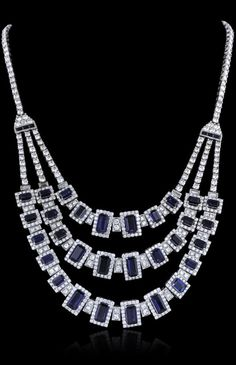 Art Deco 18KT White Gold 38.47ctw Sapphire and Diamond Necklace. Seventeen and three-quarter inch length necklace features three tapering sapphire and diamond fringe transitioning into a diamond ribbon, terminating in a concealed clasp with safety bar. The necklace is reminiscent of the jewelry designs from the Art Deco Period.
