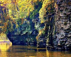 Elora Gorge in Autumn. The Grand River flows through the bottom of the Elora Gorge, in Ontario, with limestone cliffs reaching 22 metres (72 ft) high. It was formed from glacial meltwaters from the previous ice age. A former limestone quarry in the gorge can still be seen, encircled by sheer cliffs.