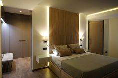 Dormitorio minimalista con vestidor al que se accede desde la pared del cabecero.  Cabecero realizado en porcelánico imitación madera con luz led en laterales. Pavimento en tarima laminada. Diseño de interiores realizado y coordinado por AZ diseño.