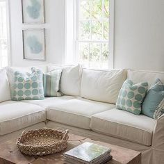 chic cottage living room features a white slipcovered sectional lined with aqua blue pillows under aqua blue sea fans facing a wood block coffee table