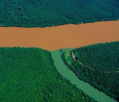 """""""Confluence of...Rio Uruguay & tributary, Misiones province, Argentina. Drastically cleared to make way for farming, the tropical rainforest of Argentina is now in some areas a less effective defense against erosion than it was in the past. The heavy rains in the province...wash the soil & carry off significant quantities of iron-rich earth into...Rio Uruguay, turning the waters a dark, reddish colour...this sediment is dumped in the estuary of...Rio de la Plata..."""" More at click-through."""