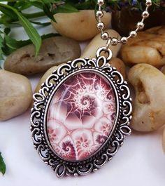 Halskette mit einer Fassung aus silberfarbenem Metall. Der Glas-Cabochon ist handgearbeitet und zeigt ein stilisiertes Muschel-Motiv.