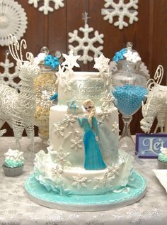 Frozen themed birthday cake by cakeglam,com Gorgeous wafer paper ruffles, 2D Elsa doll and 2D piped snowflakes.