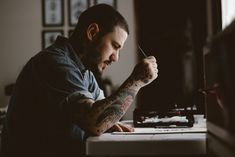 man holding pen and paper sitting near table facing outside in a dim-lit room during daytime Tattooed artist at work […] Writing Websites, Dads, Weird News, Keep Fighting, Pen And Paper, Man Photo, Essay Writing, Marketing, Artist At Work