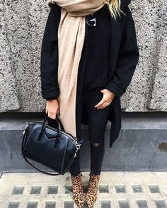 An all-black outfit with a camel scarf and leopard-print boots.