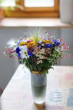 Vase of wild flowers on table