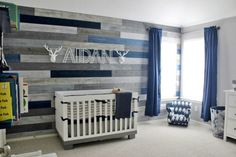Love that accent wall with the mix of wood and paint in this little boy's nursery.