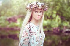 Beautiful blonde woman with flower wreath on her head - Beautiful blonde woman with flower wreath on her head. Beauty girl with flowers hairstyle. Girl in a summer forest. Fashion photo