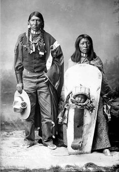 Full-length studio portrait of a Ute Native American family; Ma- Rez, the husband, stands holding a hat; his wife Ah-Ne-Pitch sits beside him with the baby Tomas-Cita in a cradleboard in front of her. Date c1899