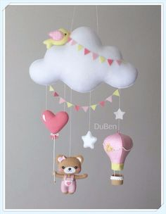 Móbile feito de feltro, costurado a mão e preenchido com fibra siliconada. Lindo móbile composto por nuvem, estrelas, um balão 3D ricamente decorado, balão de coração, um lindo passarinho e uma fofura de ursinha. Sua leveza, o seu colorido e mobilidade traz calma, distração e alegria para o se...