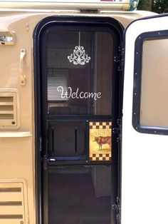 Mrs. Padilly's Completed Stenciled Screen Door with Chandelier and Welcome Sign. #Glamping http://www.mrspadillystravels.com/decorating-a-screen-door-on-casita/