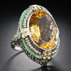 Citrine and Enamel Art Deco Ring - Sunshine on your finger! This fun, fabulous and sizable bauble, circa 1930, glistens and glows front and center with a gorgeous golden citrine. The enchanting gemstone is lavishly framed in green and yellow enamel and four tiny strands of natural freshwater pearls atop an elaborately pierced and filigreed gallery.