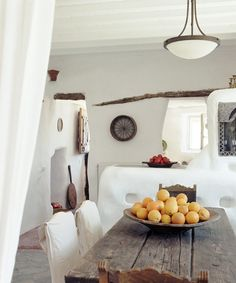 This gorgeous place is the Villa Drakothea on the Greek Island of Mykonos. Beautiful bowls w/ fruits & vegetables add color.